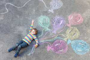 47230934 - cute little kid boy playing and flying with colorful balloons picture drawing with chalk. creative leisure for children outdoors in summer, celebrating birthday