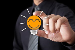 25970975 - businessman hand show light bulb with smile icon, idea concept